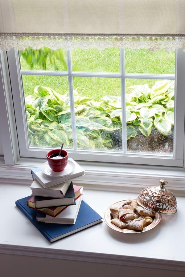Café en los libros y los pasteles llenados en la ventana foto de archivo libre de regalías