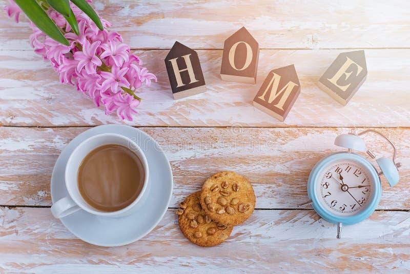 Café en tasse et biscuits blancs sur une table blanche et le réveil blanc la vue supérieure photographie stock libre de droits