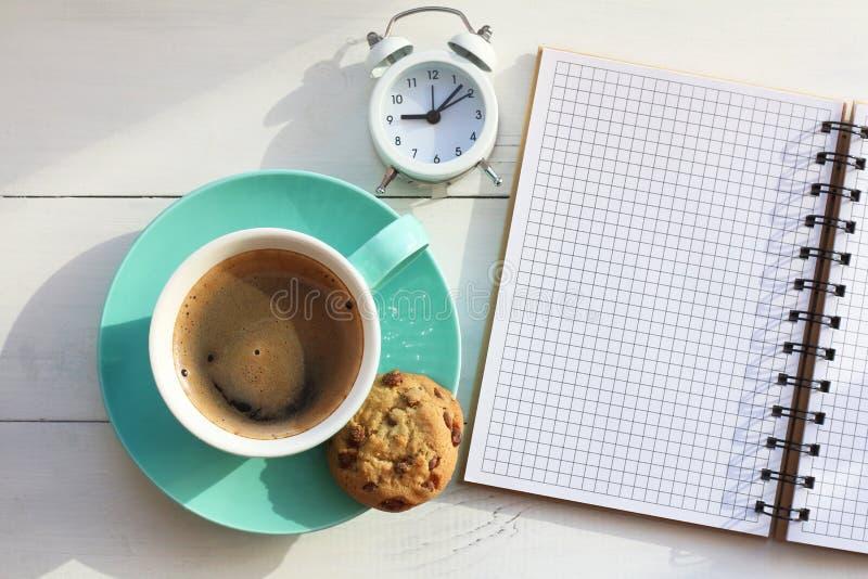 Café en tasse et biscuits de turquoise près d'un carnet sur une table blanche et le réveil blanc la vue supérieure photo stock