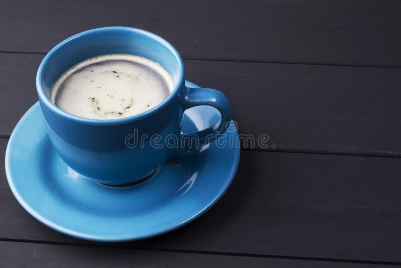 Café en taza azul con hacer juego el plato en fondo de madera negro imagenes de archivo