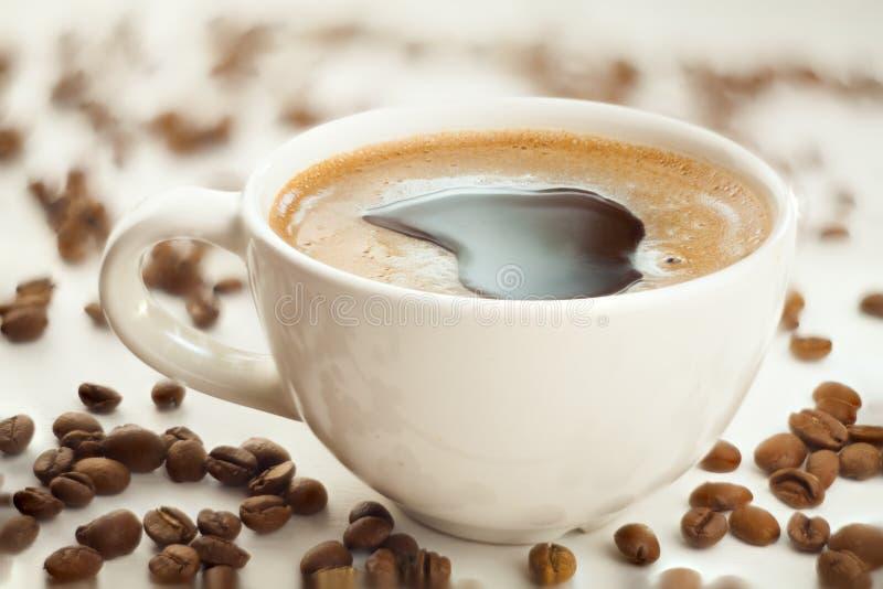 Café en taza de café con los granos naturales imagen de archivo libre de regalías