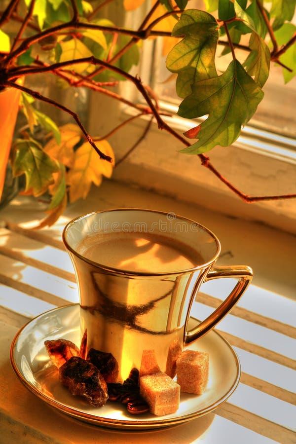 Café en taza del oro imagenes de archivo