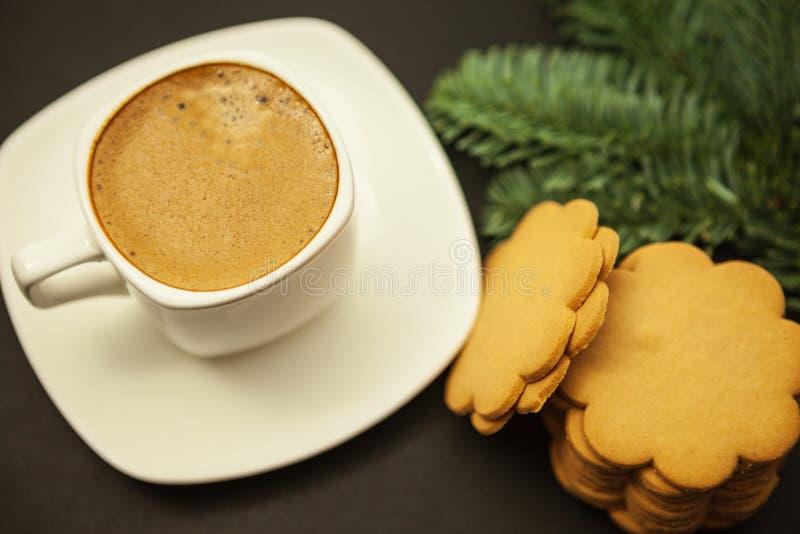Café en una taza blanca y galletas del pan de jengibre con una rama del abeto en un fondo borroso oscuro, visión superior fotos de archivo