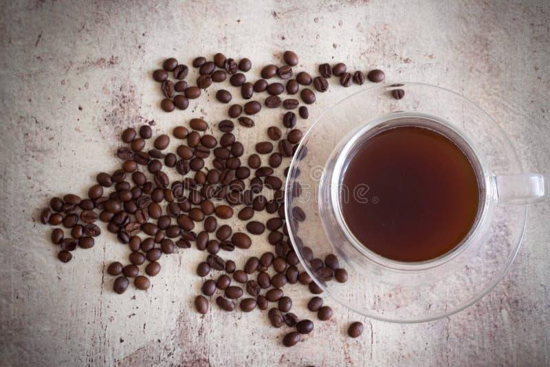 Café en una taza hermosa en la tabla entre los granos de café dispersados imagenes de archivo