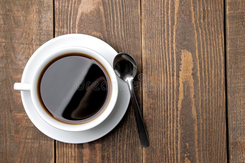 Café en una taza y una cuchara blancas en una tabla de madera marrón Visi?n superior Espacio para el texto fotos de archivo libres de regalías