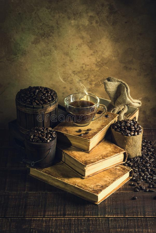 Café en verre de tasse sur de vieux livres et plancher en bois âgé photographie stock