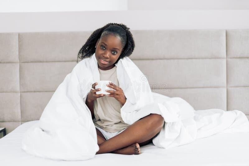 Café enjoyingmorning de la mujer hermosa feliz en la cama imagenes de archivo