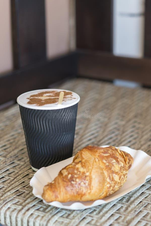 Café a entrar en una taza de papel con los cruasanes en la tabla de madera, Café a entrar en una taza de papel con los cruasanes, imagenes de archivo