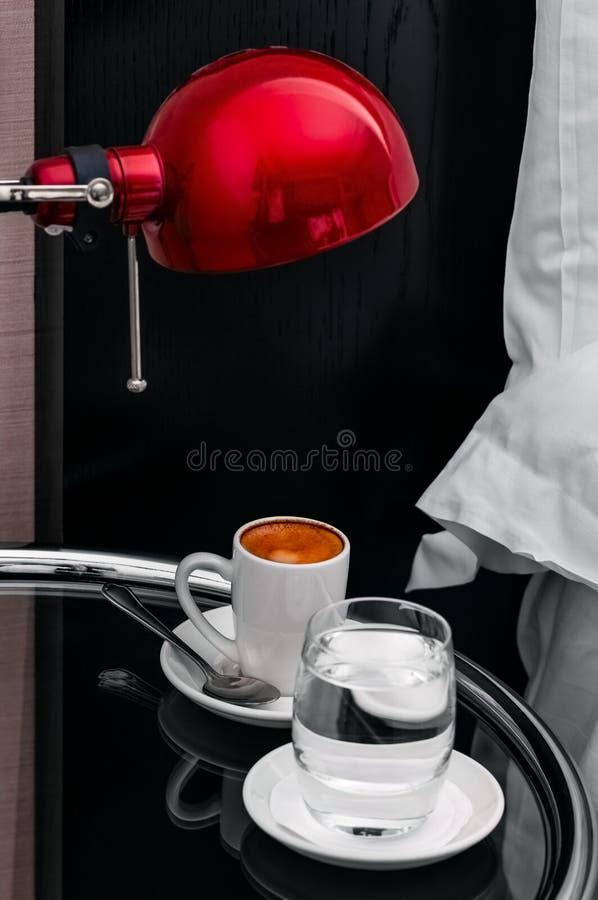 Café et l'eau d'expresso par le matin de chevet dans la chambre d'hôtel photo stock