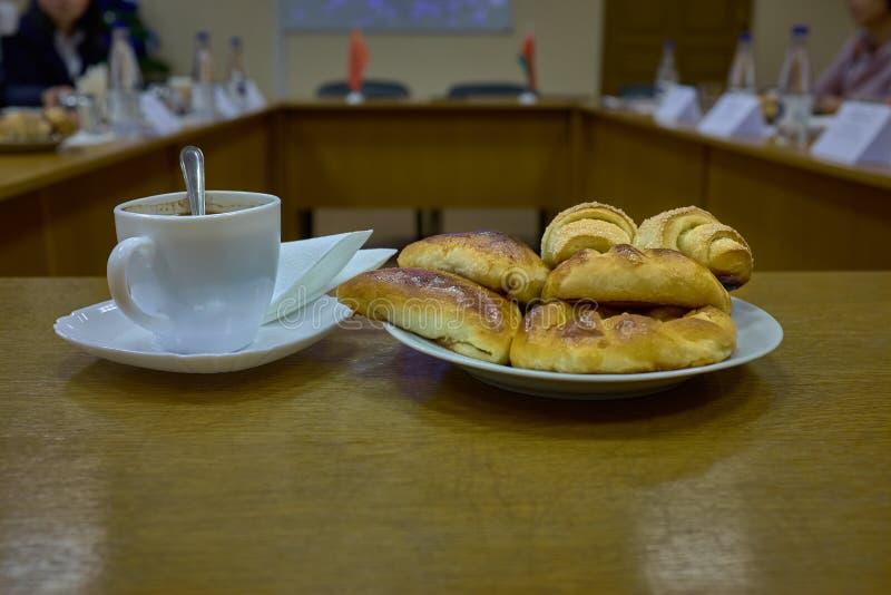 Café et petits pains frais au cours de la réunion d'affaires photos stock