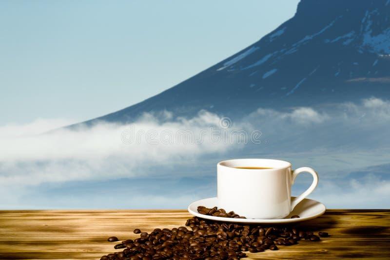 Café et tasse blanche sur la table en bois sur le fond du paysage brumeux des fjords de l'Islande collage photo stock
