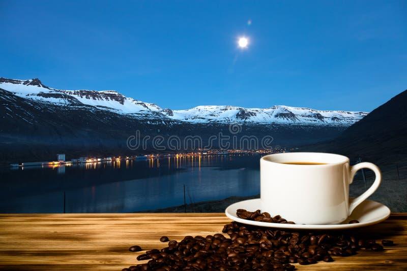 Café et tasse blanche sur la table en bois sur le fond du paysage brumeux des fjords de l'Islande collage photographie stock libre de droits