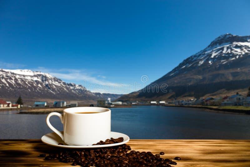 Café et tasse blanche sur la table en bois sur le fond du paysage brumeux des fjords de l'Islande collage images libres de droits