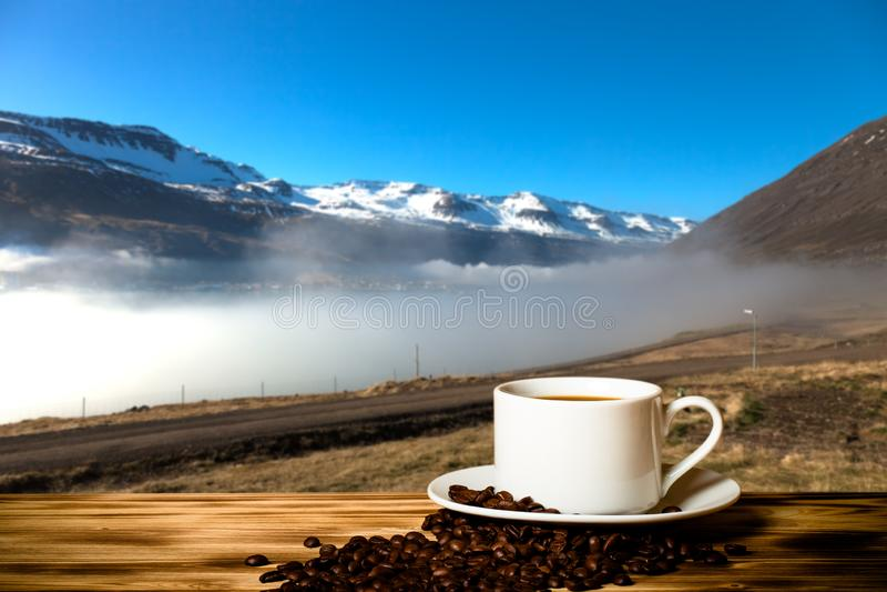 Café et tasse blanche sur la table en bois sur le fond du paysage brumeux des fjords de l'Islande collage images stock