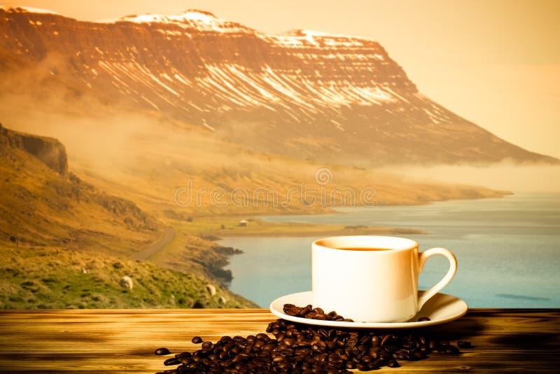 Café et tasse blanche sur la table en bois sur le fond du paysage brumeux des fjords de l'Islande collage toned photographie stock libre de droits