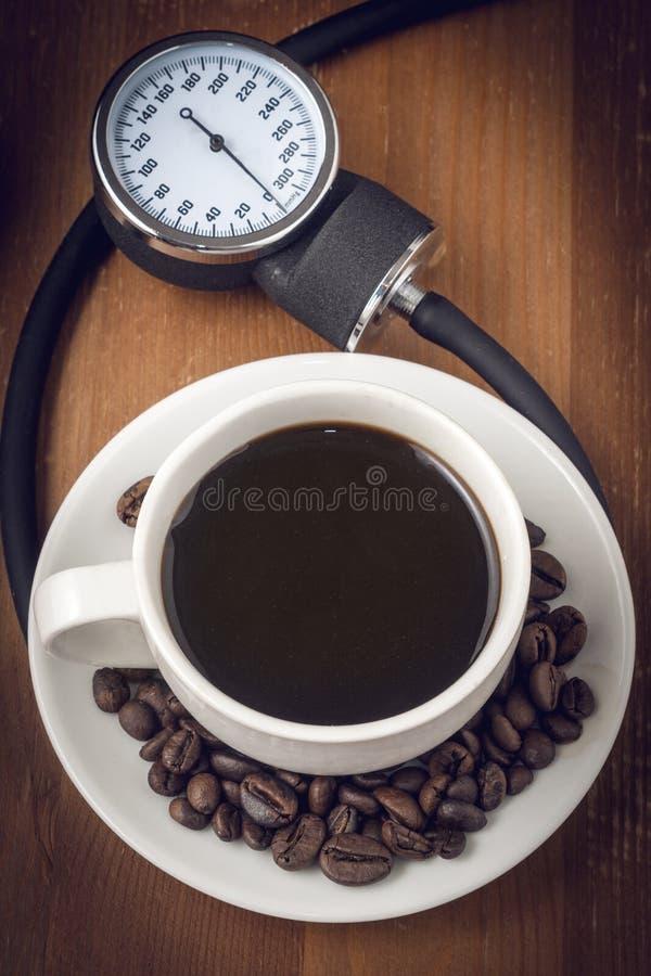 Café et tension artérielle, une image de concept avec une tasse de café sorrounded par un sphygmomanometer photographie stock
