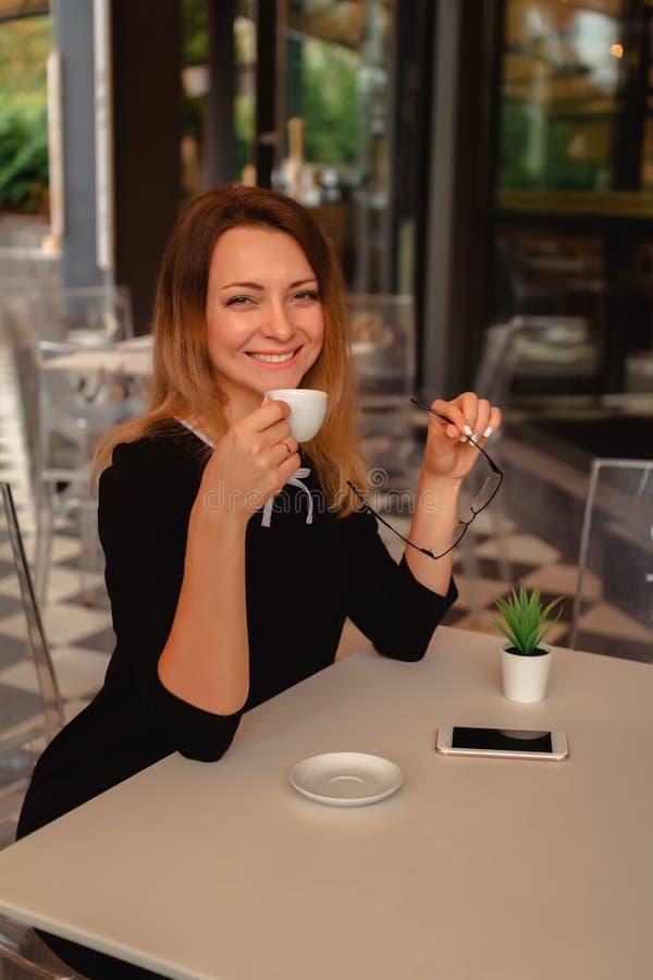 Café express de consumición femenino sonriente en el café fotos de archivo libres de regalías