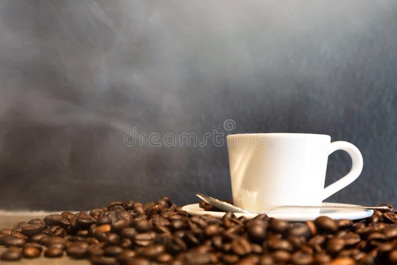 Café express en una taza de café y de granos de café calientes en fondo negro de la pared en una tienda del café, café express fr fotos de archivo