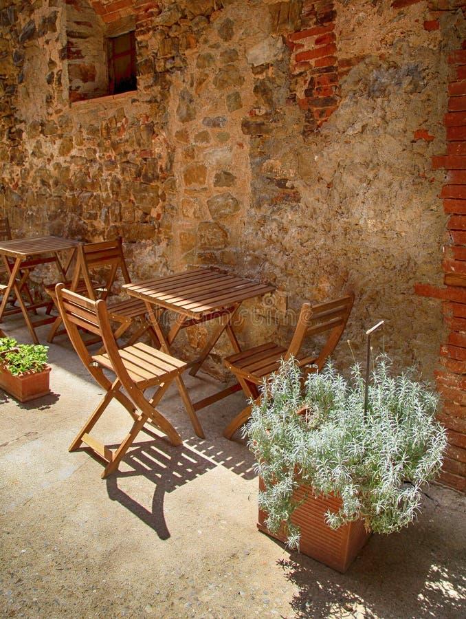 Café exterior acolhedor com tabela de madeira e cadeiras na vila pequena, fotografia de stock