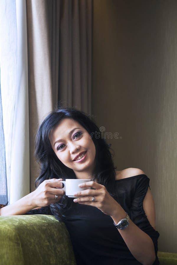 Café fêmea asiático da bebida no apartamento foto de stock