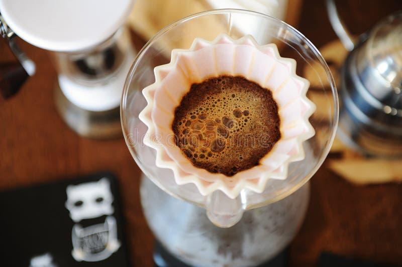 Café fleurissant dans le dispositif d'écoulement en céramique rose d'origami Vue supérieure Brassage manuel alternatif de main photographie stock