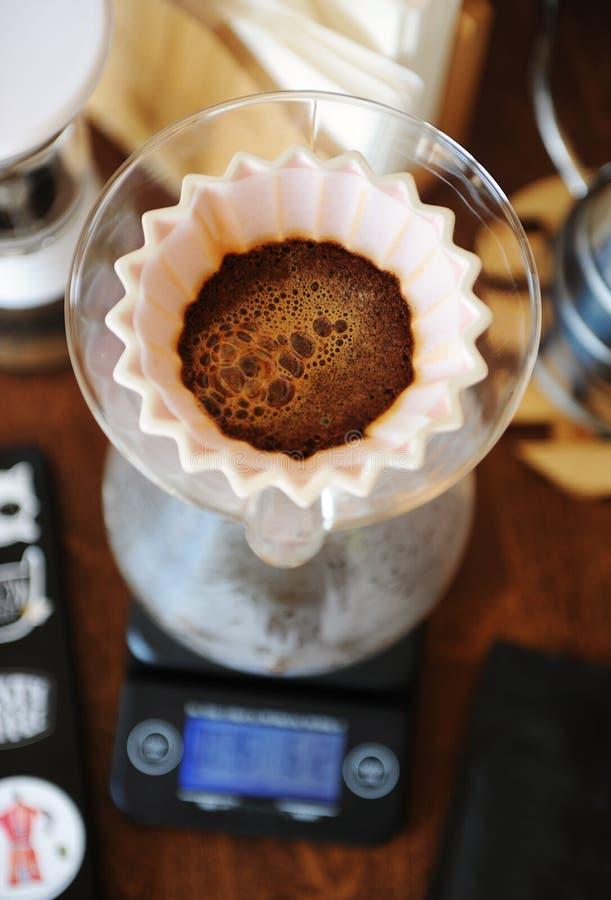 Café fleurissant dans le dispositif d'écoulement en céramique rose d'origami Vue supérieure Brassage manuel alternatif de main photos stock