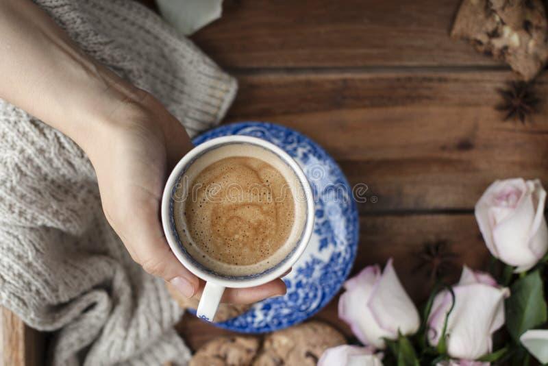 Café fragante en una mano del ` s de la mujer, un ramo de rosas blancas y intimidad del otoño Buenos días Visión superior Copie e imagenes de archivo