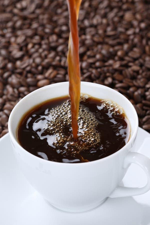 Café frais chaud se renversant dans la tasse image libre de droits