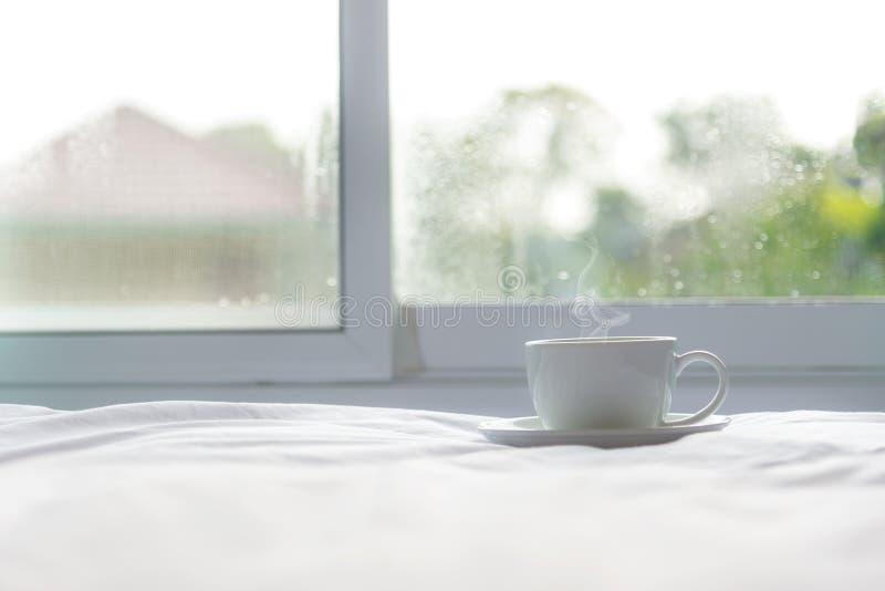 Café fresco de la mañana en la cama blanca cerca de la ventana en el día soleado, fotografía de archivo