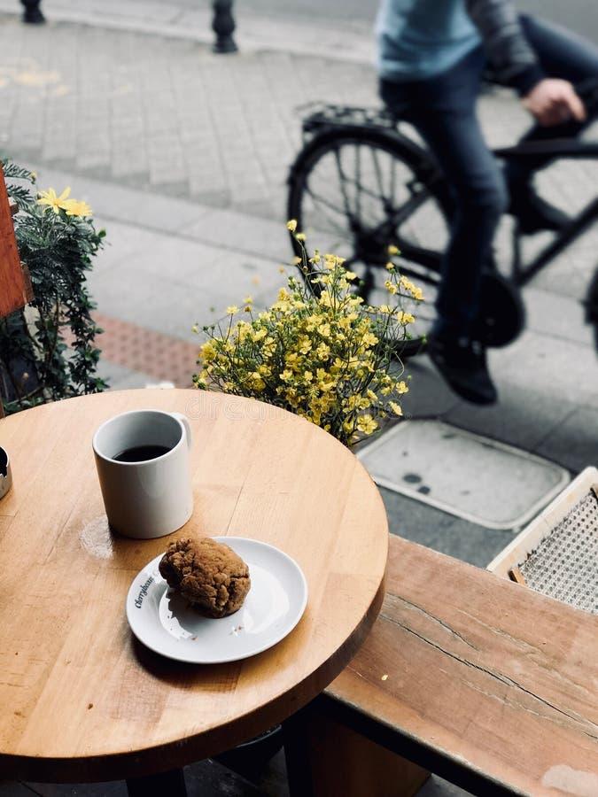 Café fresco del filtro con la galleta y las flores cerca de la calle en el concepto del fondo de Bycle de la tienda del café fotografía de archivo