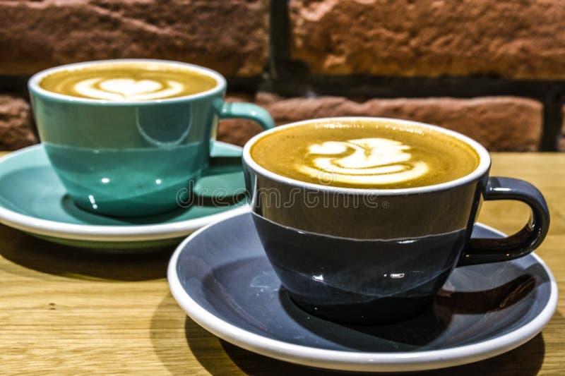 Café fresco na cafetaria Arte do Latte em um cappuccino Saboroso e belamente Dois copos em uma tabela telefone Cisne de tiragem fotos de stock