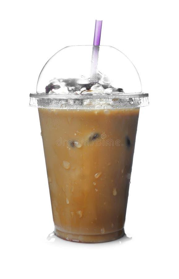 Café frio com cubos e palha de gelo no copo plástico molhado no fundo branco imagem de stock