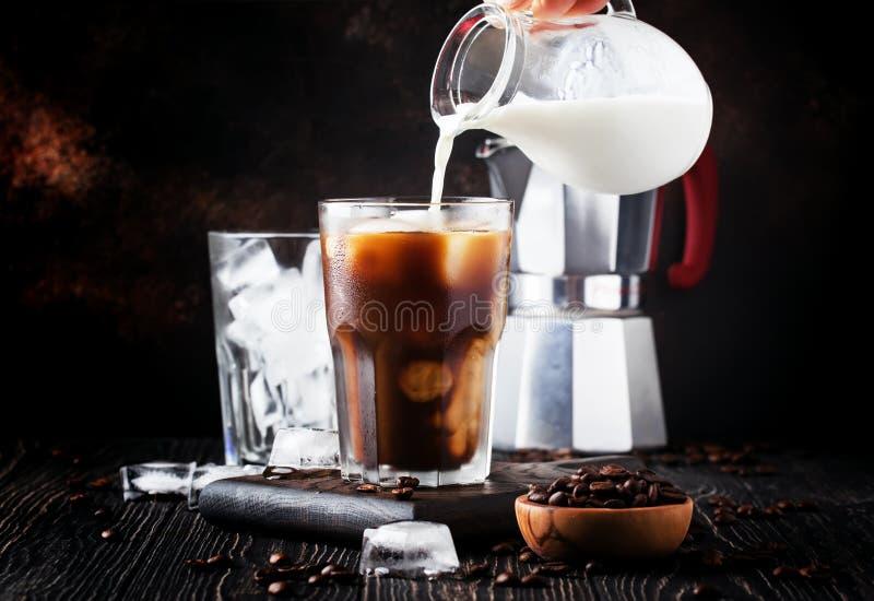 Café froid d'été avec de la glace et le lait, fond brun, selectiv images stock
