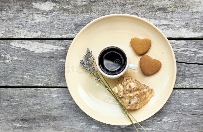 Café, galletas en forma de corazón, lavanda y una cáscara en la tabla de madera resistida vieja imagen de archivo libre de regalías