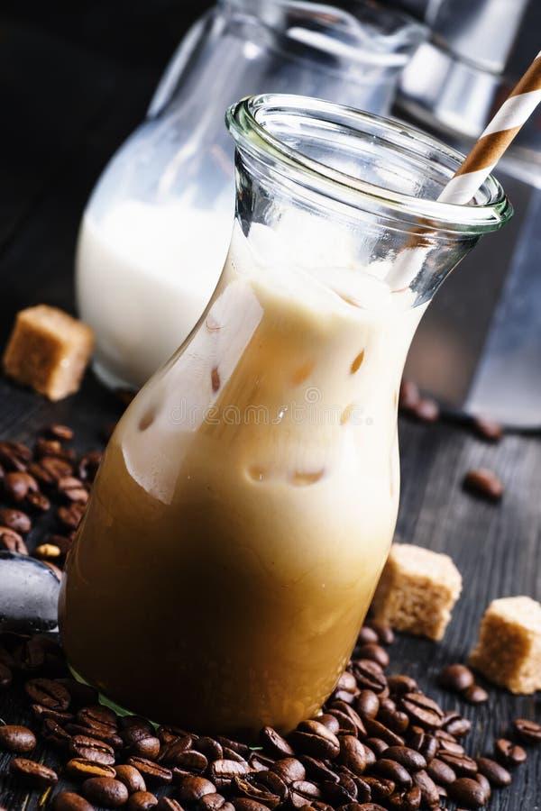 Café glacé froid avec du lait et la glace dans une cruche en verre, backgrou foncé photos stock