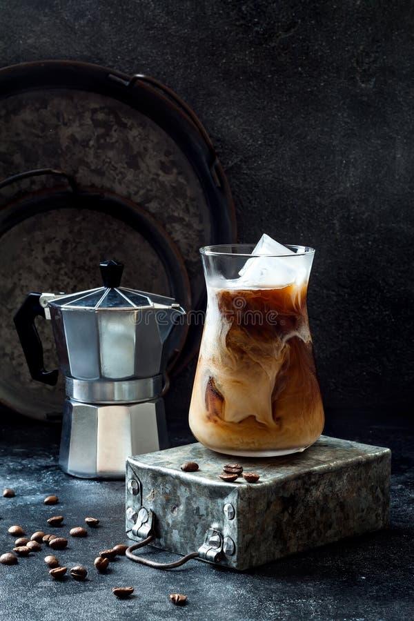 Café glacé régénérateur froid avec de la crème en verre grand et grains de café sur le fond foncé image libre de droits