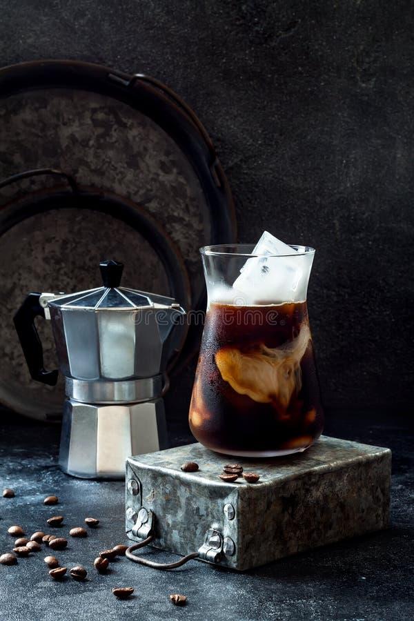 Café glacé régénérateur froid avec de la crème en verre grand et grains de café sur le fond foncé photo libre de droits