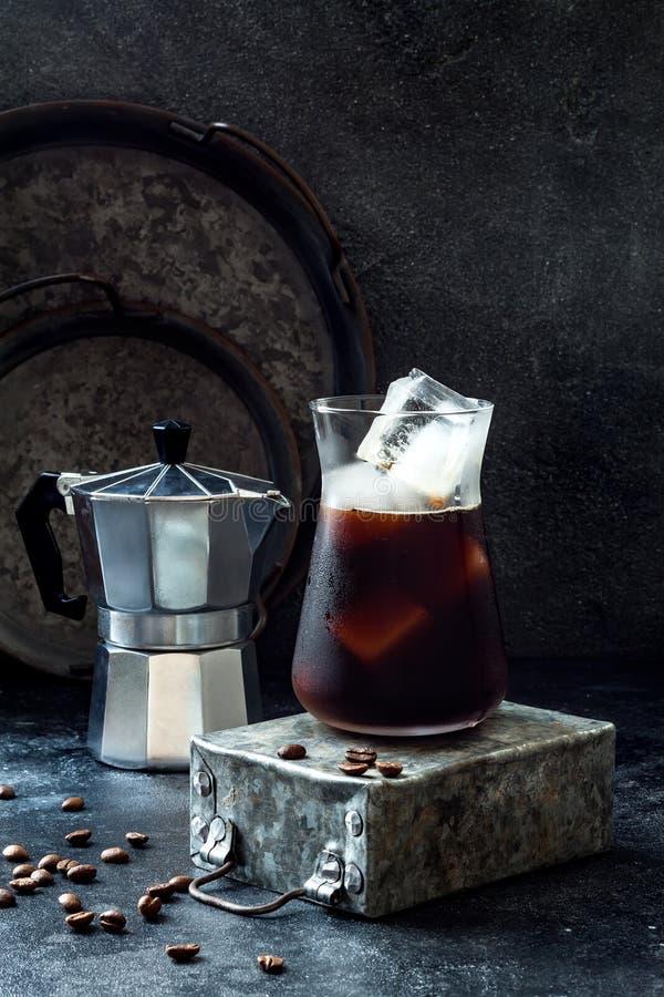 Café glacé régénérateur froid en verre grand et grains de café sur le fond foncé photos libres de droits