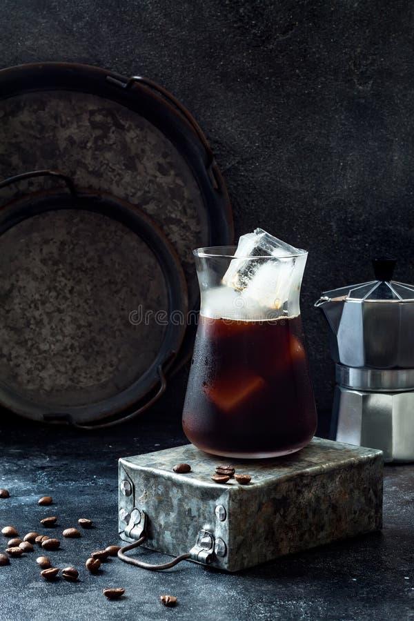 Café glacé régénérateur froid en verre grand et grains de café sur le fond foncé images libres de droits
