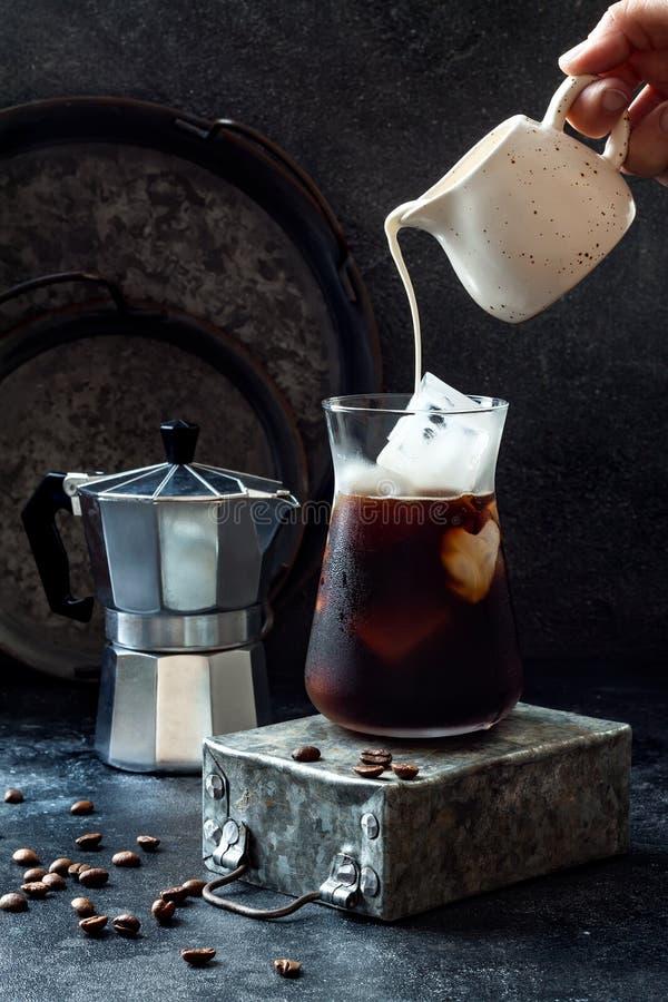 Café glacé régénérateur froid en verre grand et grains de café sur le fond foncé Crème se renversante dans le verre avec du café  photos stock