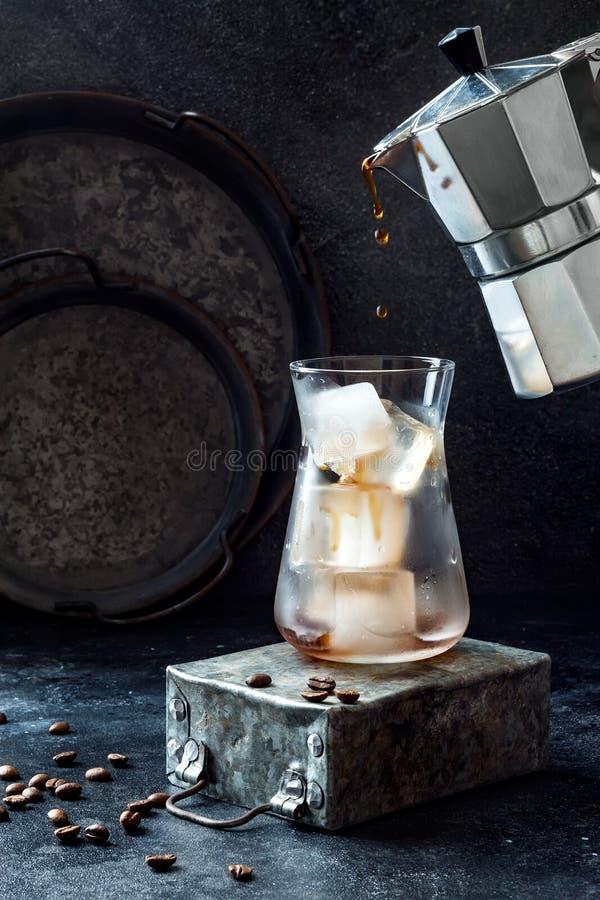 Café glacé régénérateur froid en verre grand et grains de café sur le fond foncé Café se renversant de pot de moka dans le verre  photo libre de droits