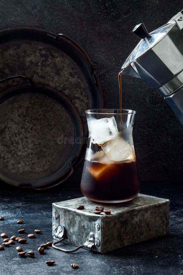 Café glacé régénérateur froid en verre grand et grains de café sur le fond foncé Café se renversant de pot de moka dans le verre  photos libres de droits