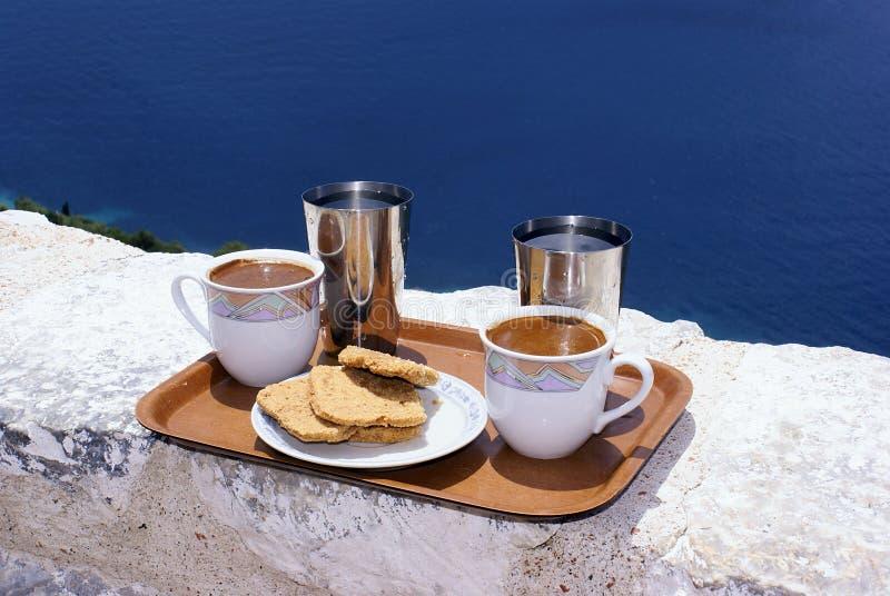 Café grego na parede e no mar azul fotos de stock royalty free