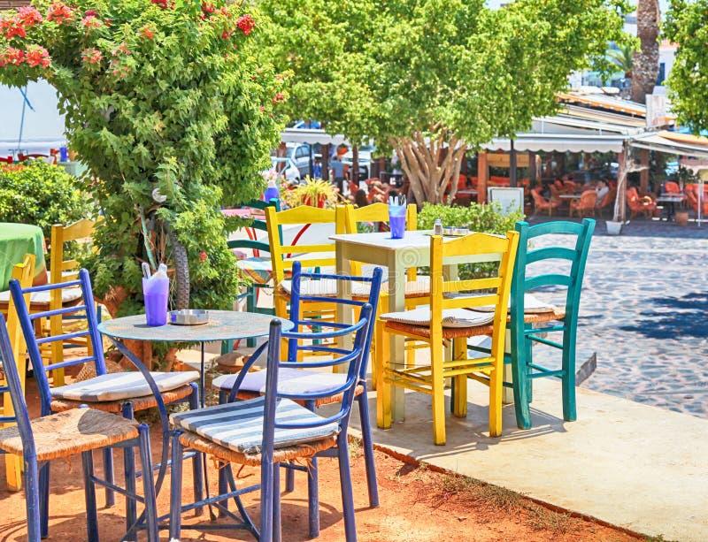 Café griego de la acera tradicional con las tablas multicoloras y el ch fotos de archivo libres de regalías