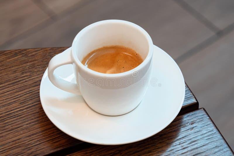 Café italiano em um copo cerâmico branco com pires em uma tabela de madeira marrom Fundo de Brurred imagem de stock