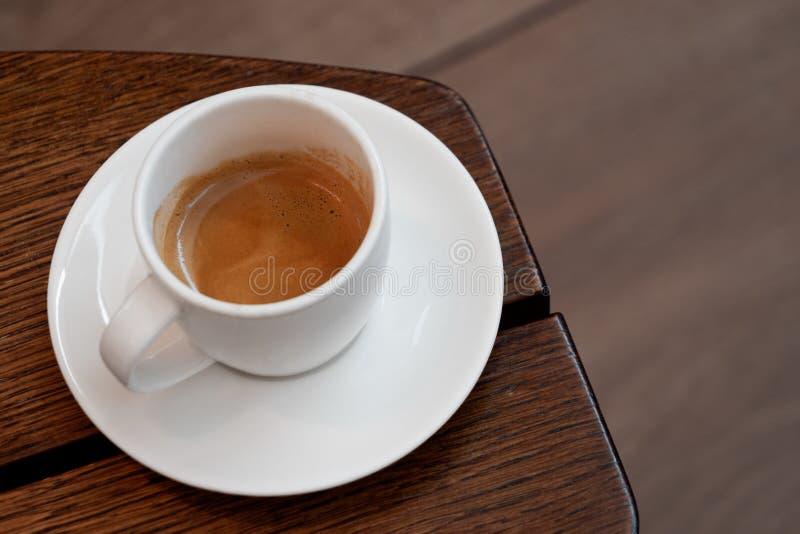 Café italiano em um copo cerâmico branco com pires em uma tabela de madeira marrom Fundo de Brurred fotografia de stock