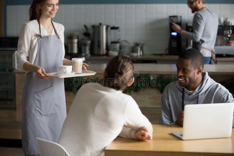 Café joven sonriente del servicio de la camarera a los visitantes masculinos del café imagen de archivo libre de regalías