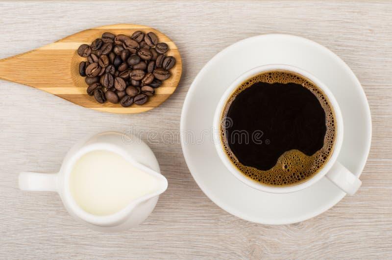 Café, leche del jarro y cuchara de madera con los granos de café fotos de archivo libres de regalías