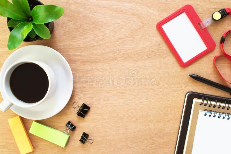 Café, libro, paperclip, lápiz, tarjeta del empleado, post-it y pote del árbol en el escritorio de madera marrón rústico Espacio d fotografía de archivo