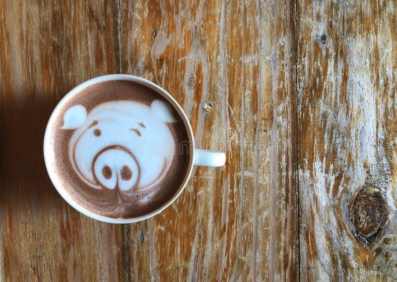 Café lindo del arte del latte de la cara del cerdo en la taza blanca en la tabla de madera fotos de archivo